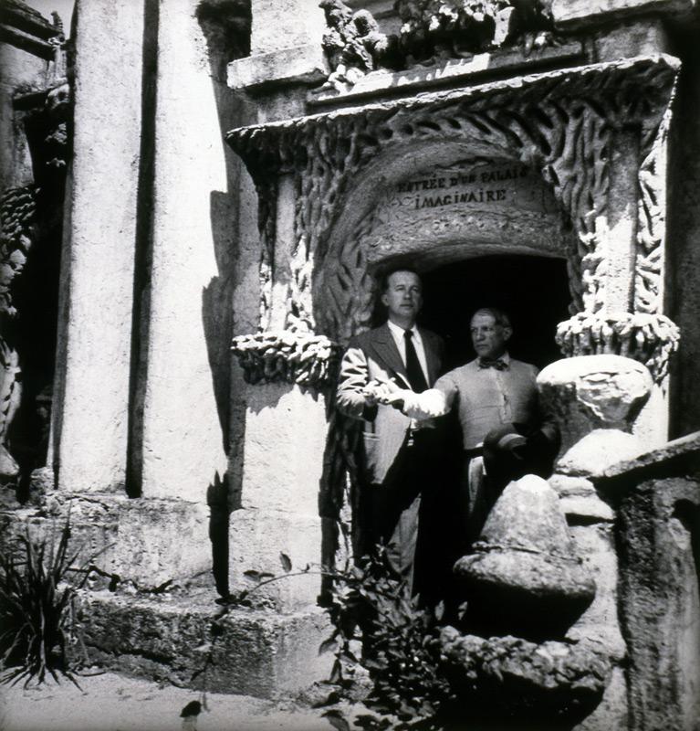 Picasso et Eluard à l'entrée du Palais idéal du Facteur Cheval, pris en photo par Dora Maar en 1937. Les deux hommes se tiennent une main