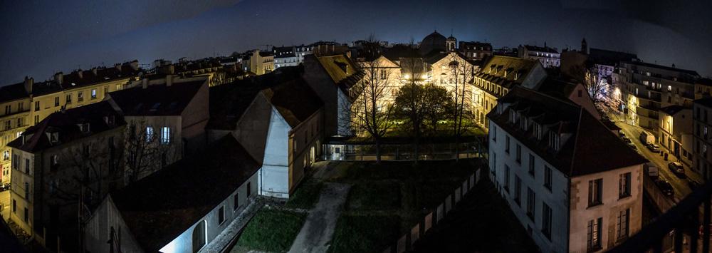 photographie nocturne en grand angle et en plongée des bâtiments du musée, un cloître et un clocher