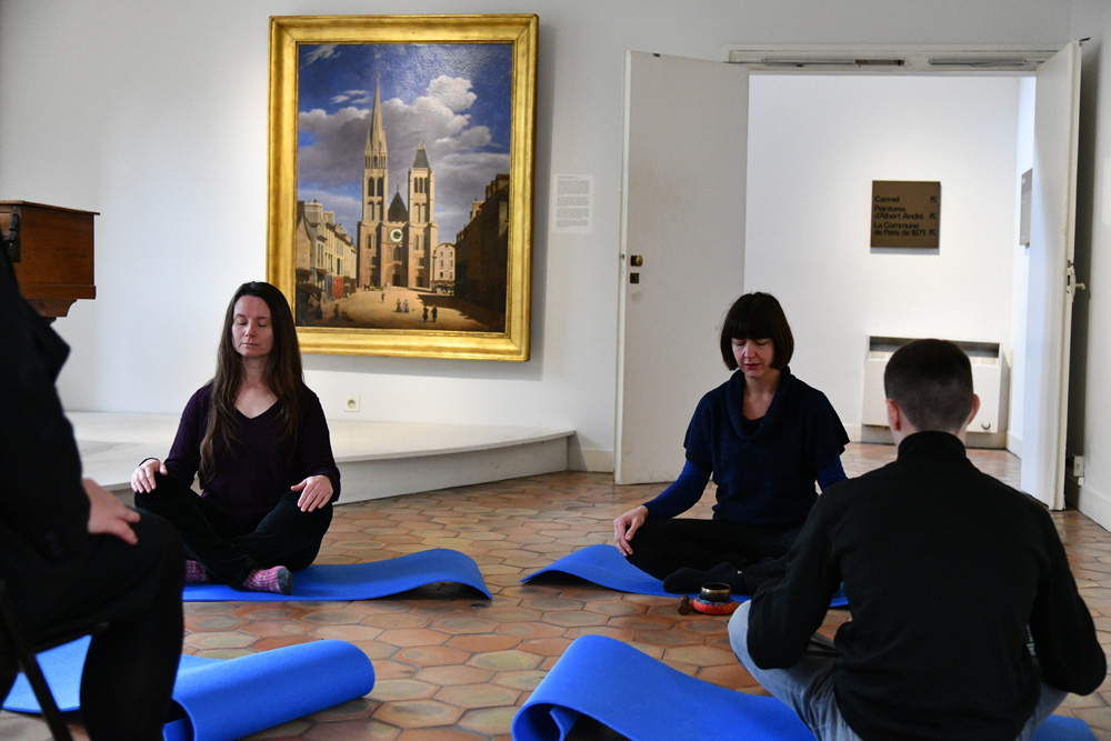 4 personnes lors d'une visite méditative, assises en tailleur sur des tapis de yoga, les yeux fermés pendant que l'instructrice les guide par la voix