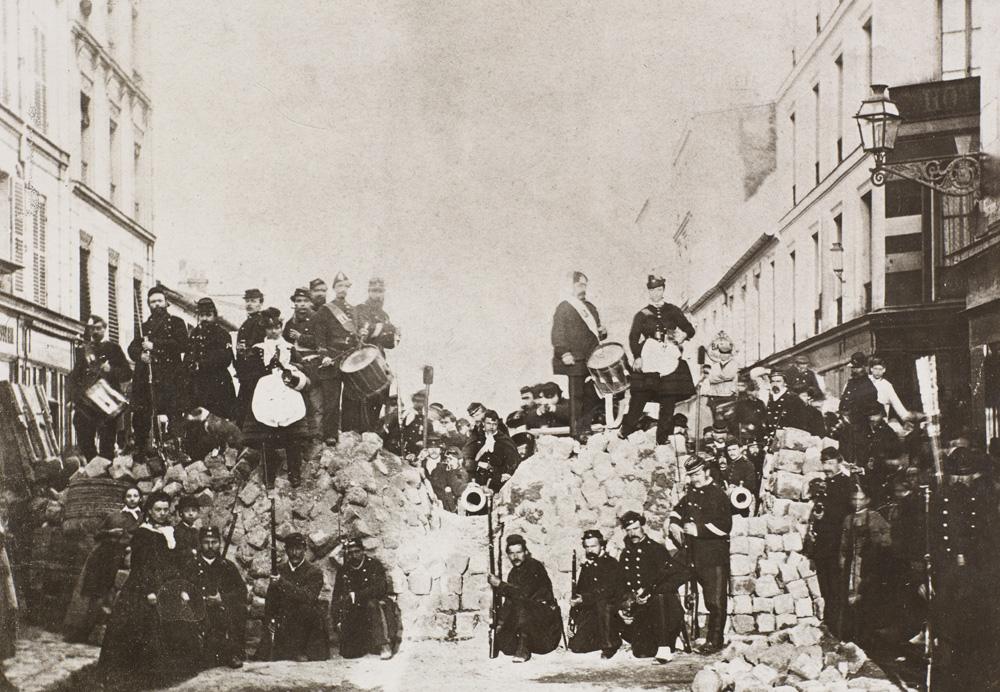 photographie noir et blanc d'une barricade rue de Charonne pendant la Commune de Paris en 1871. Des hommes et des femmes posent en costume militaire, avec des armes