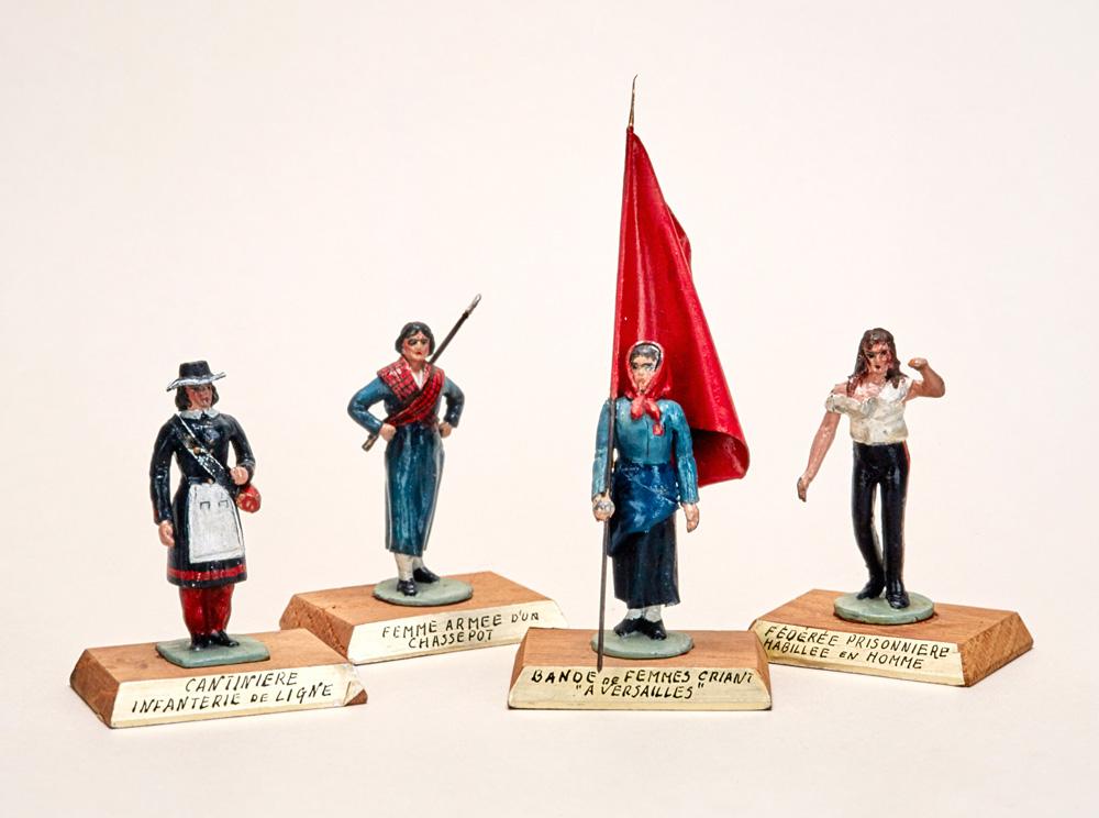 4 figurines en plomb de femmes combattantes de la commune dont une au centre porte un grand drapeau rouge