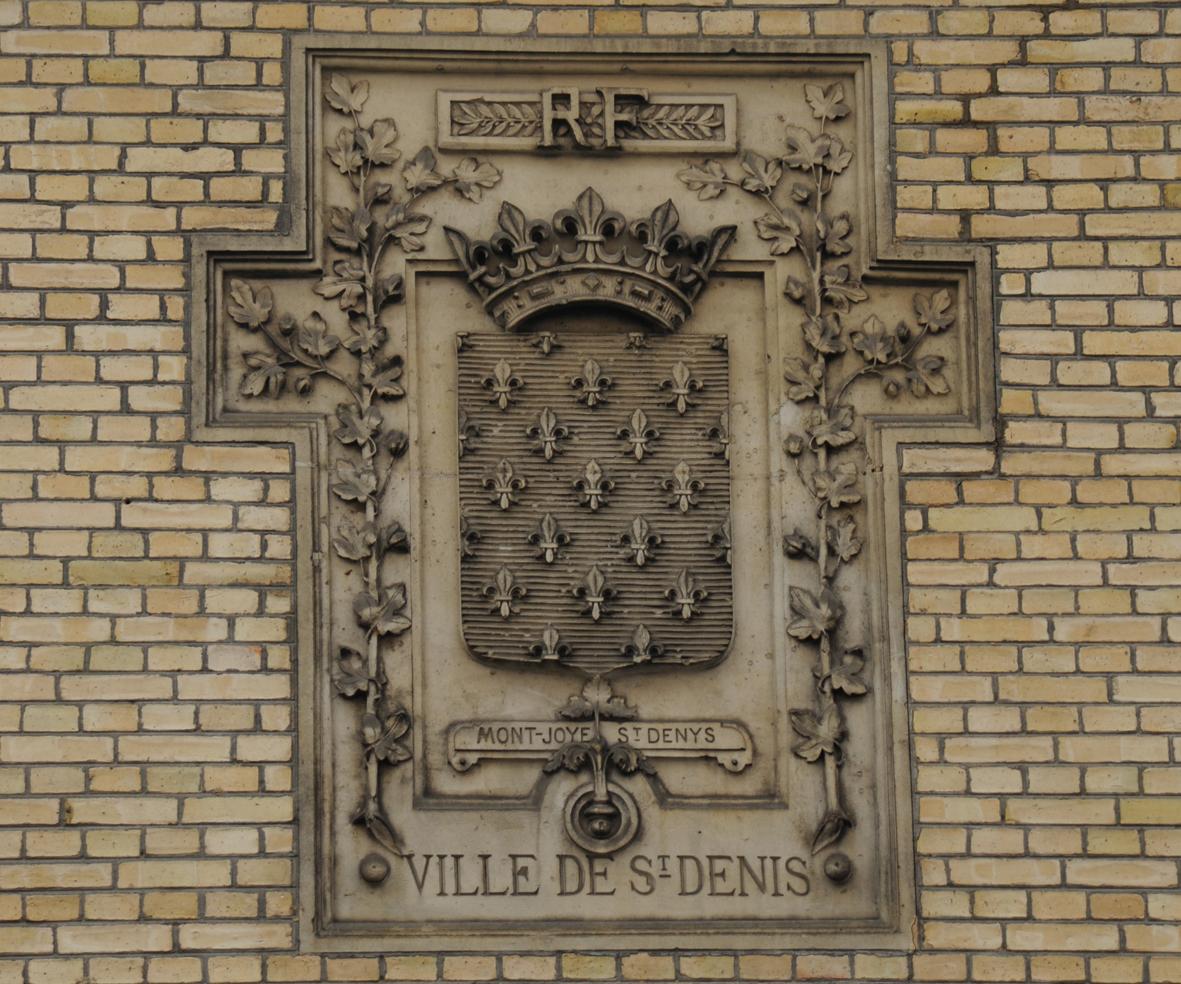 Blason de Saint-Denis sur la façade de l'Unité d'archéologie, rue Franciade : « d'azur semé de fleurs de lys d'or » Document UASD, photo : J. Mangin